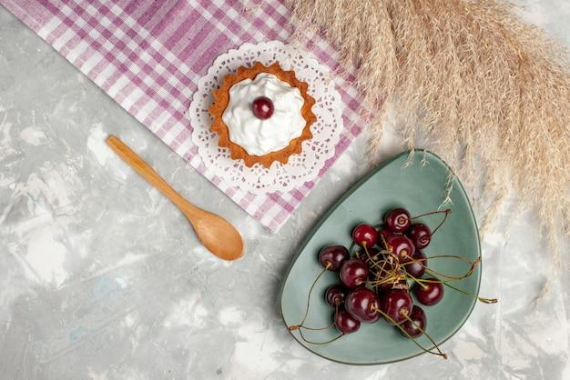Вид сверху маленький сливочный торт со свежей вишней на светлом столе торт чай фрукты сладкие сливки