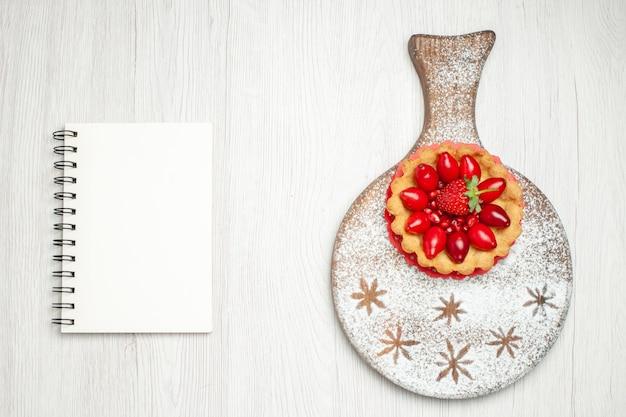 Vista dall'alto piccola torta cremosa con frutta fresca sulla scrivania bianca
