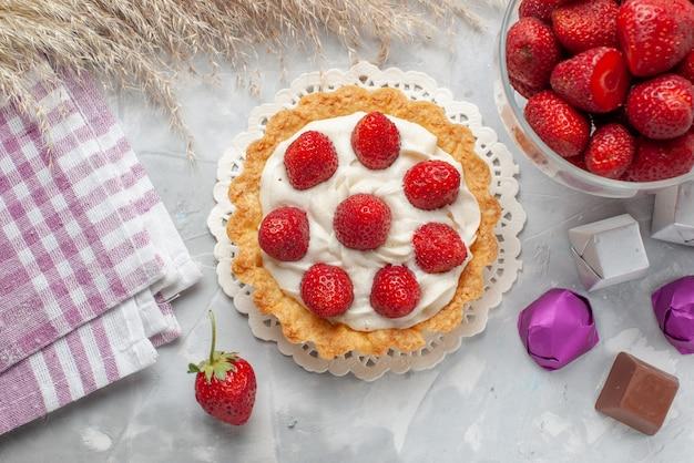 Вид сверху маленький сливочный торт со свежей красной клубникой и шоколадными конфетами на белом настольном пироге с фруктово-ягодным бисквитным кремом