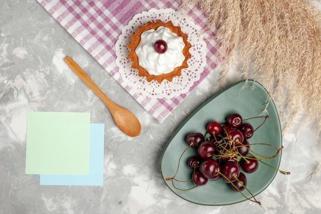 トップビュー明るい背景に新鮮なサワーチェリーと小さなクリーミーなケーキフルーツケーキ甘い焼きクリーム