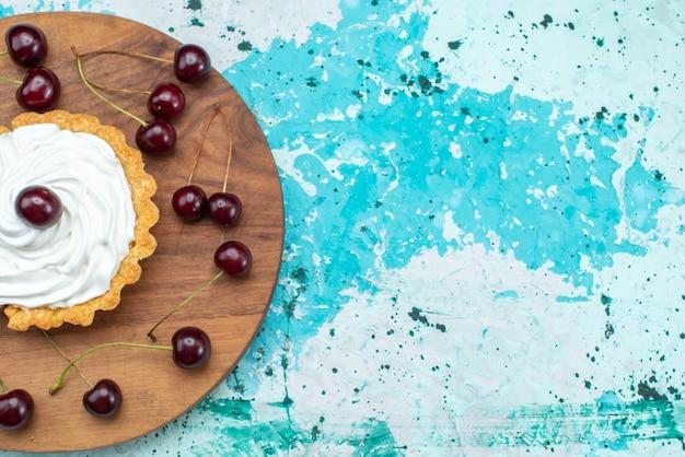 밝은 파란색 배경에 신선한 신 체리와 상위 뷰 작은 크림 케이크 과일 케이크 크림 파이 달콤한 설탕 색상