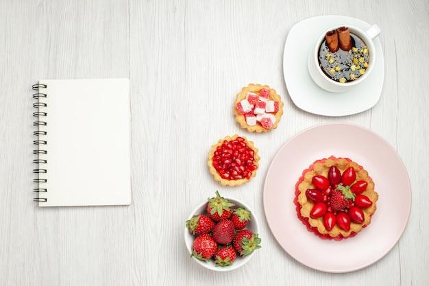 Вид сверху маленький сливочный торт с фруктами и чашкой чая на белом столе