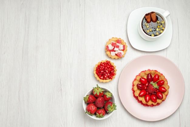 흰색 책상에 과일과 차 한잔과 함께 상위 뷰 작은 크림 케이크