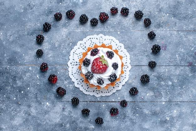 明るい机の上のハート型のブラックベリーと一緒にラズベリーと小さなクリーミーなケーキの上面図フルーツベリーケーキビスケットの写真