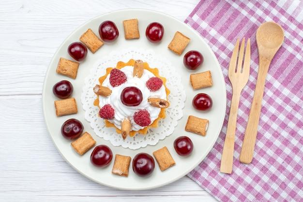 Вид сверху маленький сливочный торт с малиной и маленьким печеньем на белом столе фруктовый торт сладкий ягодный крем
