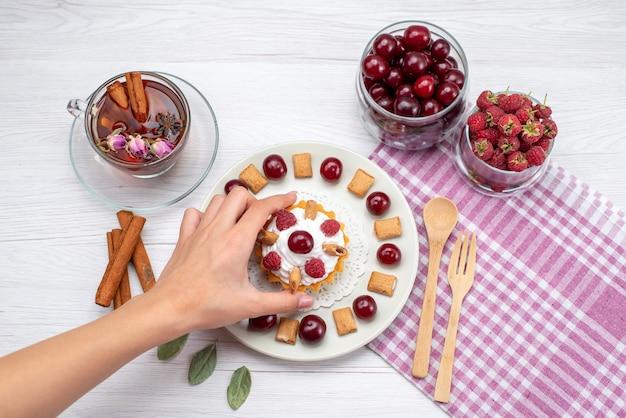 Вид сверху маленький сливочный торт с малиной, вишней и маленьким печеньем, чай с корицей на светлом столе, фруктовый торт, ягодный крем, сахарный чай