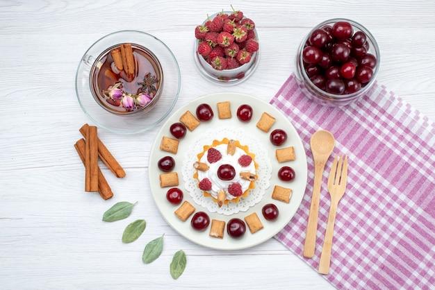 Вид сверху маленький кремовый торт с малиной, вишней и маленьким печеньем, чай с корицей на белом столе, фруктовый торт, сладкий ягодный крем