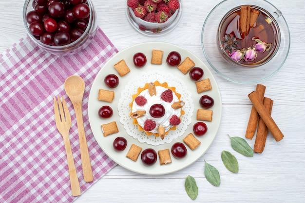 上面図ラズベリーチェリーと小さなビスケットティーシナモンが白いライトデスクにある小さなクリーミーなケーキフルーツケーキスイートベリー