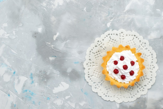 Top view little creamy cake with red fruits on the grey surface sweet