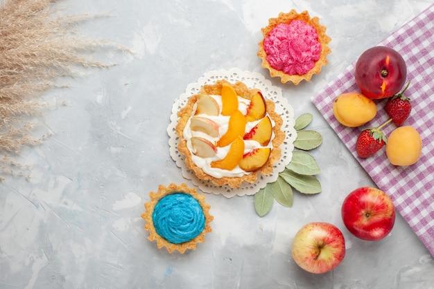 トップビュースライスしたフルーツと白いクリームとクリーミーなケーキとライトホワイトのデスク上のフルーツと小さなクリーミーなケーキフルーツケーキビスケットクッキー甘い
