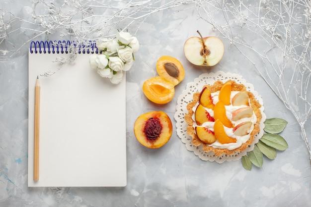 トップビュースライスしたフルーツと白いクリームと新鮮なアプリコットと桃のメモ帳と白いライトデスクフルーツケーキビスケットクッキーの小さなクリーミーなケーキ