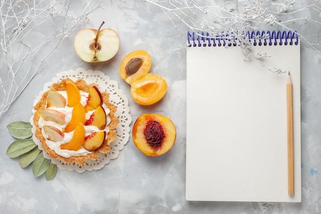 Вид сверху маленький сливочный торт с нарезанными фруктами и белым кремом вместе со свежими абрикосами и персиками на белом столе фруктовый торт бисквитное печенье