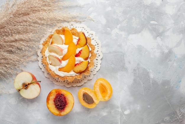 Вид сверху маленький сливочный торт с нарезанными фруктами и белым кремом вместе со свежими абрикосами и персиками на столе с белым светом фруктовый торт бисквитное печенье