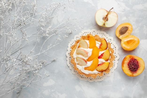 上面図スライスしたフルーツと白いクリームと白いライトデスクの新鮮なアプリコット桃と小さなクリーミーなケーキフルーツケーキビスケットクッキー焼き