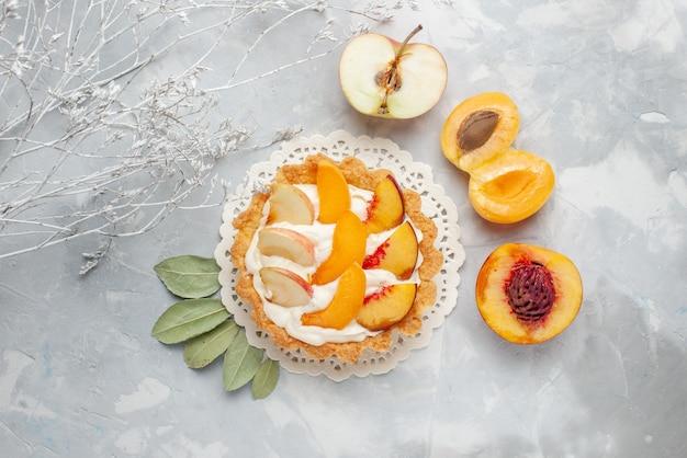 上面図スライスしたフルーツと白いクリームと新鮮なアプリコットと桃が白いライトデスクにある小さなクリーミーなケーキフルーツケーキビスケットクッキー