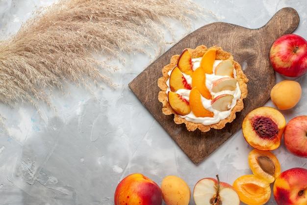 平面図ライトホワイトのデスクフルーツケーキビスケット甘い夏に新鮮な果物と一緒にスライスされたフルーツと白いクリームと小さなクリーミーなケーキ