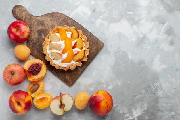 Вид сверху маленький сливочный торт с нарезанными фруктами и белым кремом вместе со свежими фруктами на светло-белом столе фруктовый торт бисквитный сладкий