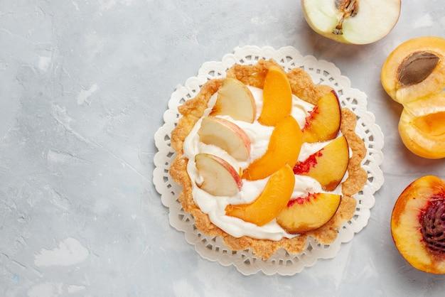 上面図ホワイトライトデスクにスライスしたフルーツと白いクリームが入った小さなクリーミーなケーキフルーツケーキの甘さビスケットクッキー焼き