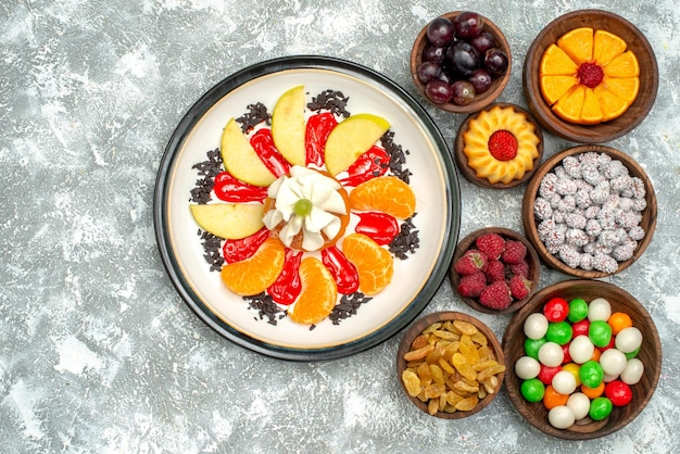 Vista dall'alto piccola torta cremosa con frutta a fette caramelle e uvetta su superficie bianca torta di frutta dolce torta di zucchero biscotto
