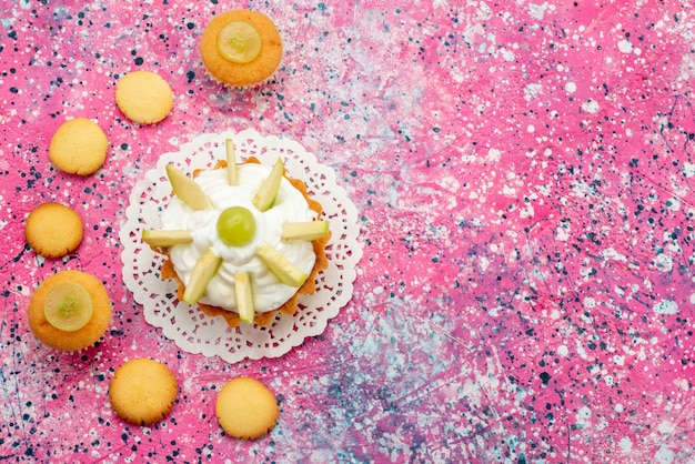 Vista dall'alto piccola torta cremosa con biscotti di frutta a fette sulla foto a colori di zucchero dolce torta colorata da scrivania