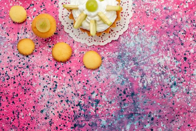 Vista dall'alto piccola torta cremosa con biscotti di frutta a fette sulla foto a colori di zucchero dolce torta colorata scrivania