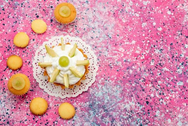 Вид сверху маленький сливочный торт с нарезанными фруктами печенье на цветном столе торт сладкое сахарное цветное фото