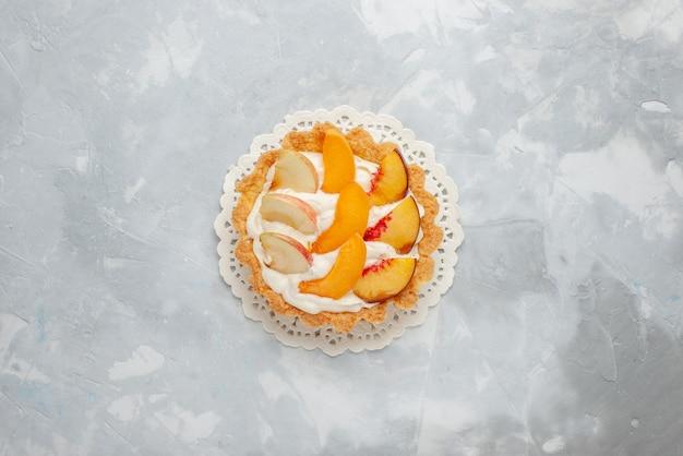 明るい背景のフルーツケーキ甘いビスケットクッキーにスライスされたフルーツとその上に小さなクリーミーなケーキの上面図