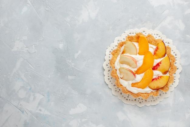 上面図白い背景の上のスライスされた果物とその上に小さなクリーミーなケーキフルーツケーキ甘いビスケットクッキー