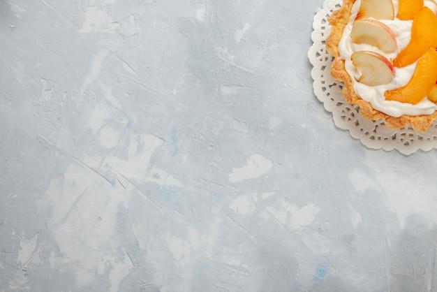 上面図白い机の上のスライスされた果物とその上に小さなクリーミーなケーキフルーツケーキ甘いビスケットクッキー