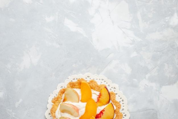 上面図ホワイトライトデスクにスライスしたフルーツが乗った小さなクリーミーなケーキフルーツケーキ甘いビスケットクッキーの味