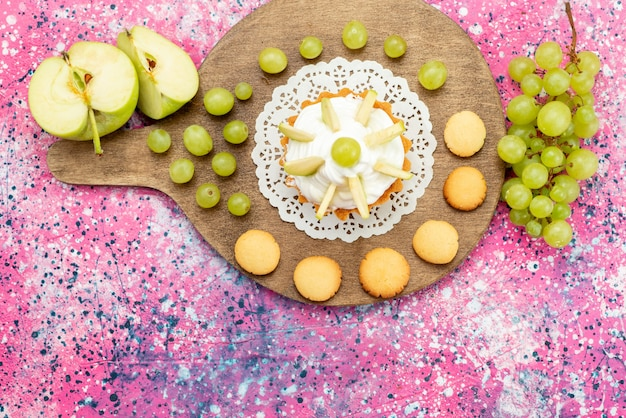 上面図色付きのデスクケーキにスライスしたフルーツと小さなクリーミーなケーキ甘い砂糖焼き写真