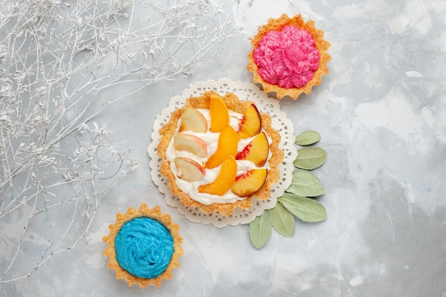 Vista dall'alto piccola torta cremosa con frutta a fette e crema bianca insieme a torte cremose sulla scrivania leggera torta di frutta biscotto biscotto dolce
