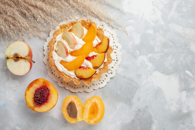 Vista dall'alto piccola torta cremosa con frutta a fette e crema bianca insieme ad albicocche fresche e pesche sul biscotto biscotto alla frutta bianca luce
