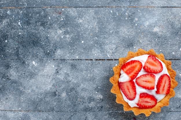 Вид сверху маленький сливочный торт с нарезанной клубникой на сером фоне письменный фруктовый торт сладкого цвета
