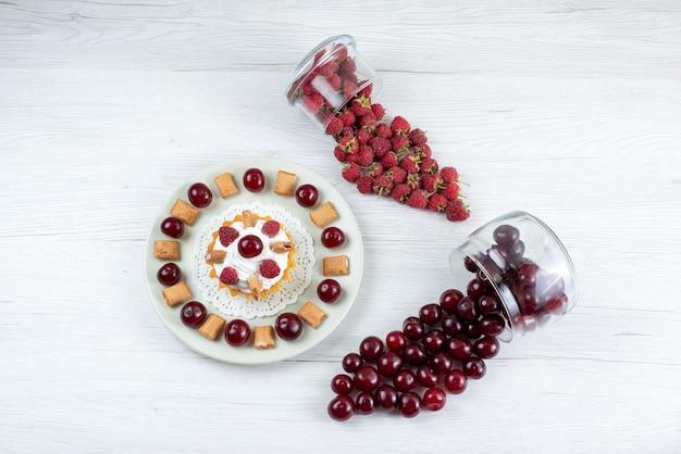 Вид сверху маленький сливочный торт с вишней и малиной на светлом фоне свежие фрукты ягодный торт сладкий