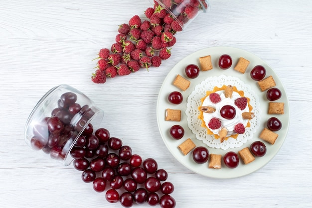 平面図ライトホワイトのテーブルにサワーチェリーとラズベリーの小さなクリーミーなケーキフレッシュフルーツベリーケーキ甘い