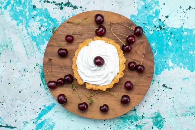 上面図水色の背景のケーキ甘いビスケットクリームにサワーチェリーと小さなクリーミーなケーキ