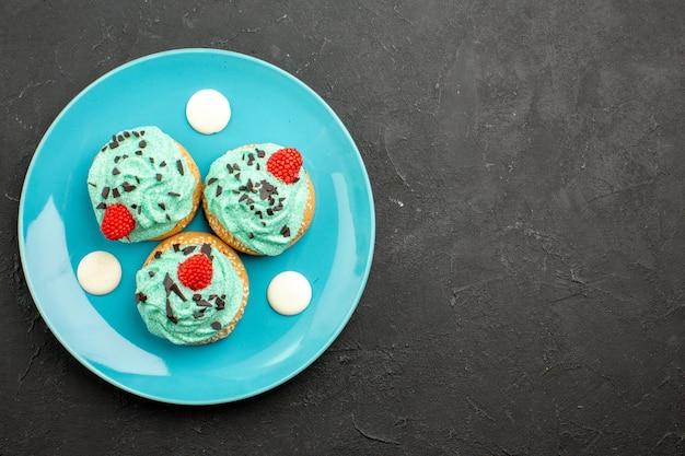 Вид сверху маленькие сливочные пирожные вкусные сладости к чаю внутри тарелки на темной поверхности кремовый торт бисквитный десерт чайный цвет