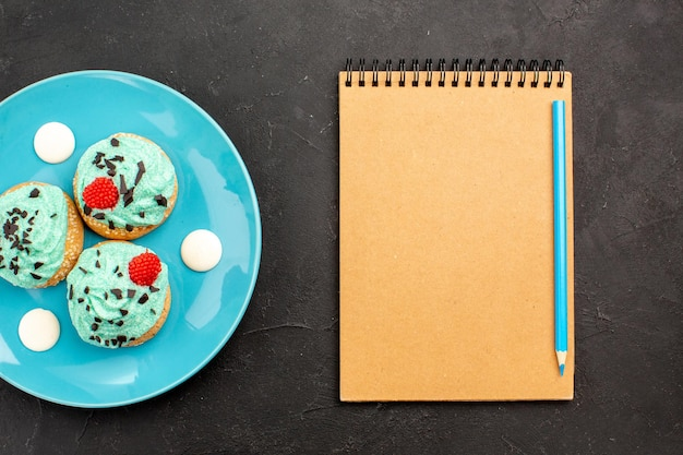 짙은 회색 표면 차 크림 케이크 비스킷 디저트 색상에 있는 접시 안에 있는 차를 위한 작은 크림 케이크 맛있는 과자