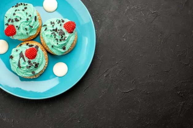 Top view little creamy cakes delicious sweets for tea inside plate on dark floor cream cake biscuit dessert tea color