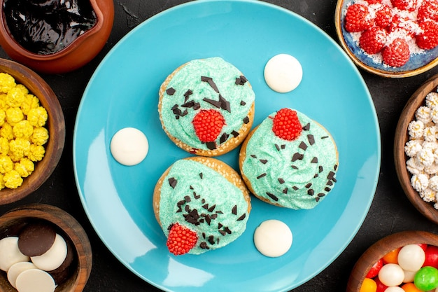 Top view little creamy cakes with candies on the dark grey surface dessert cake biscuit color candy cookie