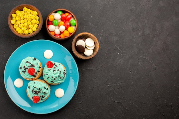 Top view little creamy cakes with candies on dark surface dessert cake biscuit color candy cream