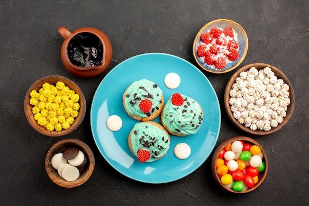 トップビューダークグレーの表面にキャンディーが付いた小さなクリーミーなケーキデザートケーキビスケットカラーキャンディークッキー