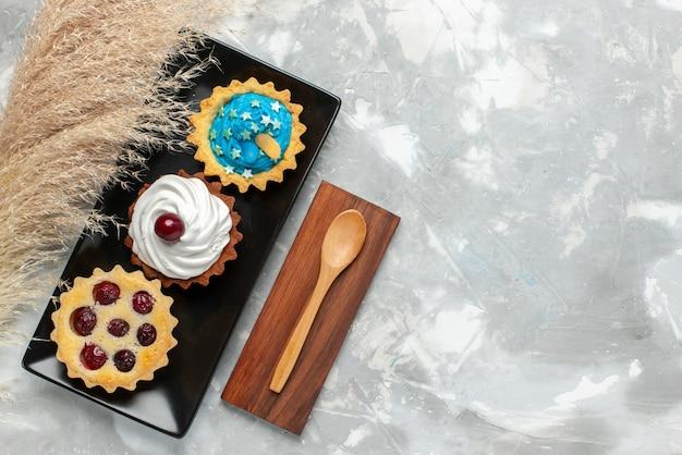 Vista dall'alto piccole torte cremose con panna e frutta sulla crema di biscotti dolci torta sfondo chiaro