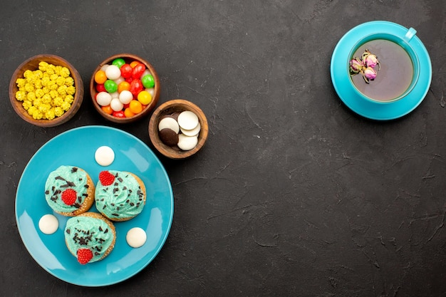 Top view little creamy cakes with cup of tea and candies on dark surface tea cream cake biscuit dessert color candy