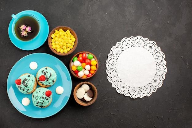 Vista dall'alto piccole torte cremose con una tazza di tè e caramelle sulla superficie scura torta alla crema di tè biscotto dessert colore Foto Gratuite
