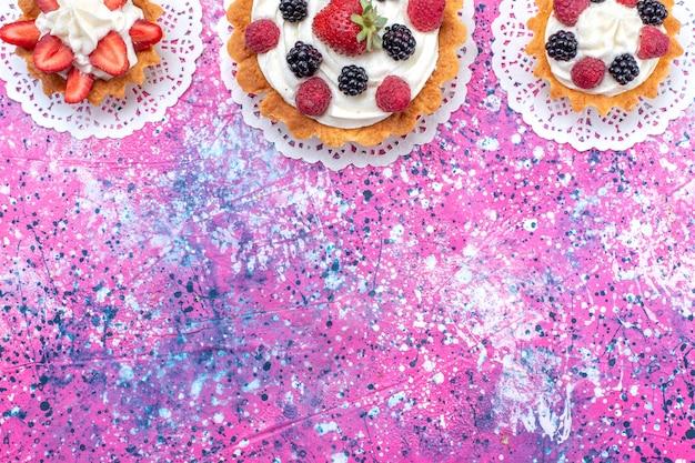 Вид сверху маленькие сливочные пирожные с разными ягодами на светлом фоне торт бисквитный ягодный сладкий выпечка
