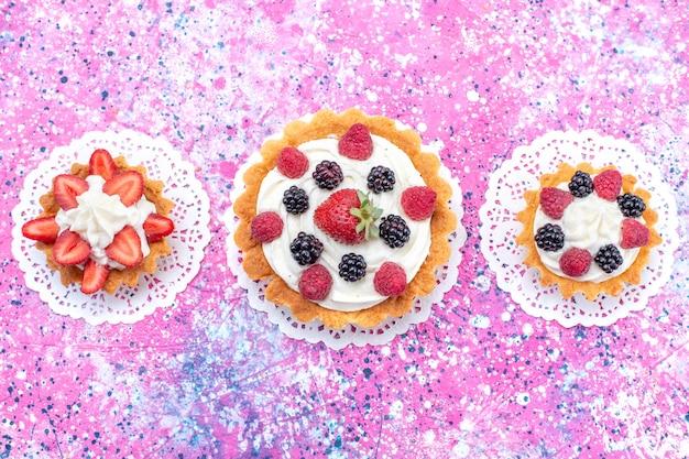 Вид сверху маленькие кремовые пирожные с разными ягодами на светло-розовом столе, бисквитно-ягодный сладкий пирог