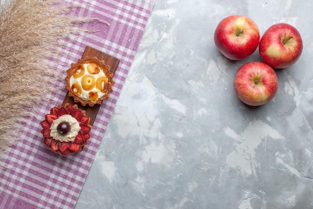 トップビュー白い机の上の新鮮な赤いリンゴと小さなクリーミーなケーキフルーツケーキビスケットクリーム甘い