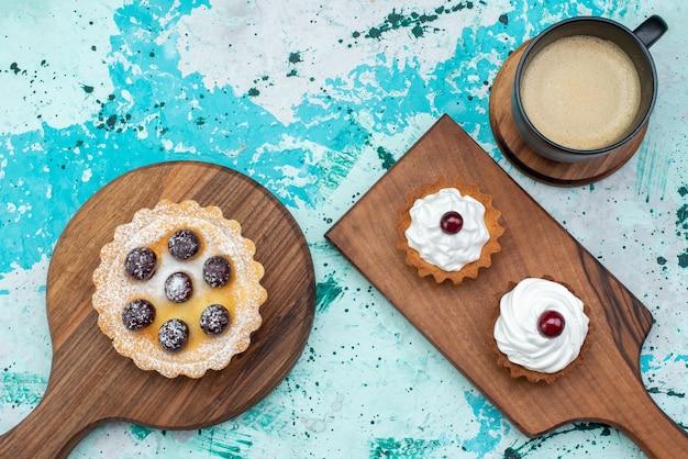Vista dall'alto piccole torte cremose con latte sullo sfondo azzurro torta dolce crema di zucchero cuocere colore